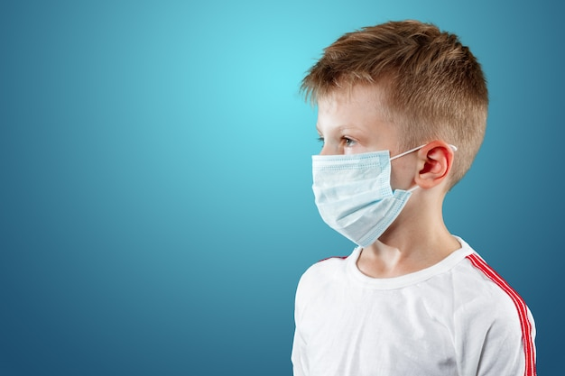 Little boy, a child in a medical mask on a blue