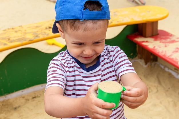 Маленький мальчик, ребенок играет в песочнице с лопатой и плесенью