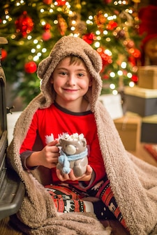 A little boy in christmas pajamas sits near a christmas tree