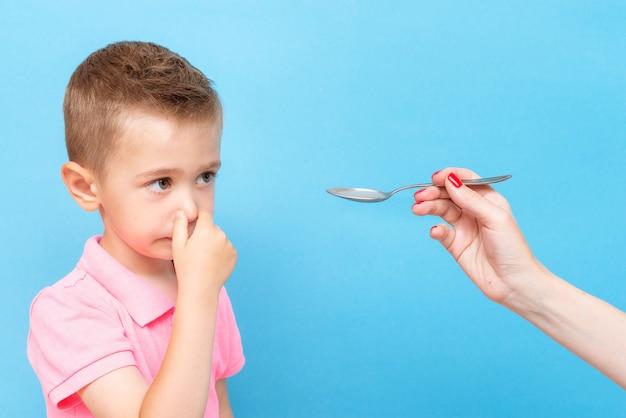 小さな男の子は彼の手で彼の鼻をクランプし、薬を飲むことを拒否します