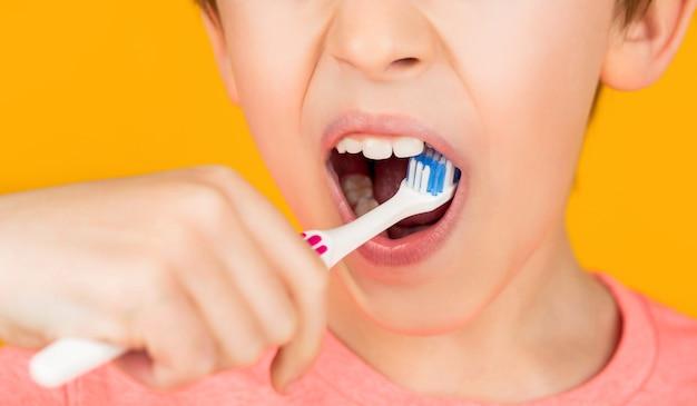 어린 소년이 어린이 칫솔로 치아를 청소합니다. 치아 위생.