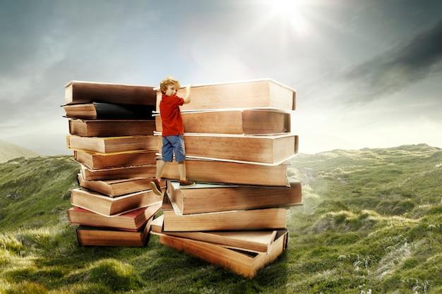 大きな本でできた塔に登る少年。子供の頃の夢、読書と教育の概念。不思議な世界。抽象的なコラージュ