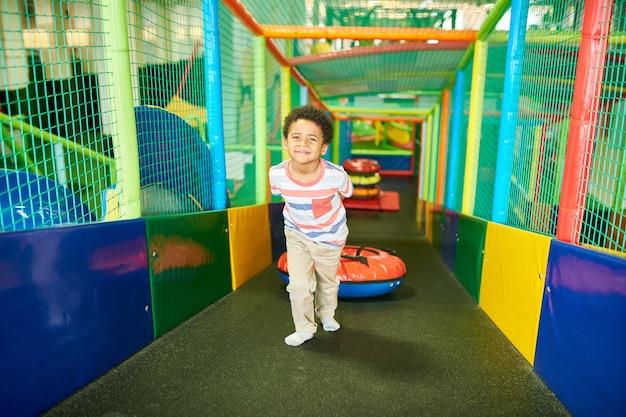 プレイセンターの小さな男の子のクライミングスライド