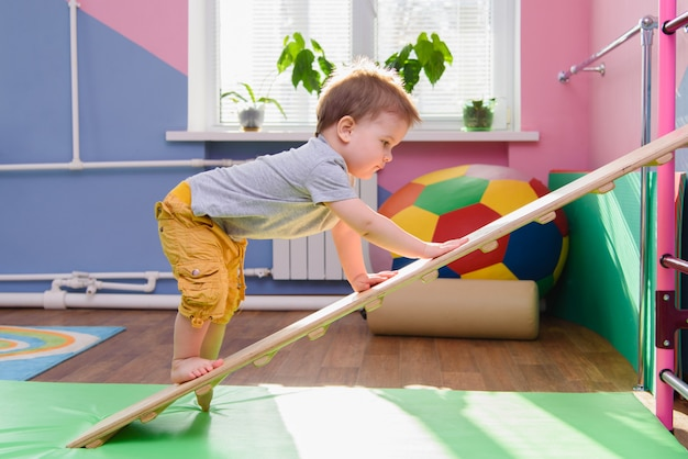 The little boy climbs up a wooden plate in the gym