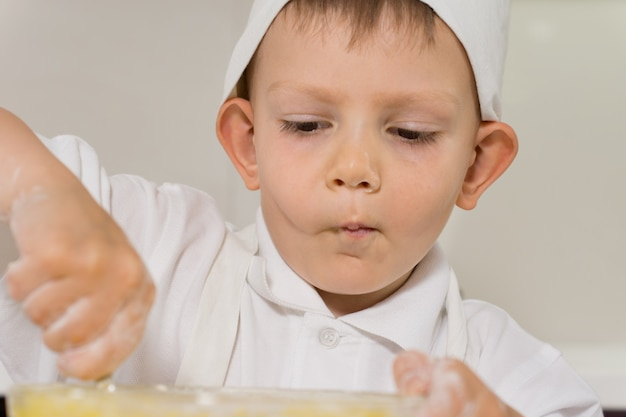 Little boy concentrating as he bakes a cake