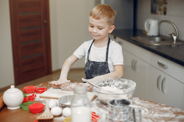 Little boy cook the dough for cookies