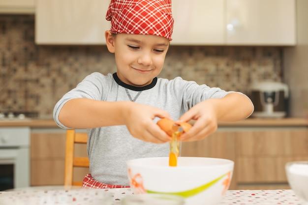 Маленький мальчик приготовления пищи. ребенок разорвать яйцо в миску.