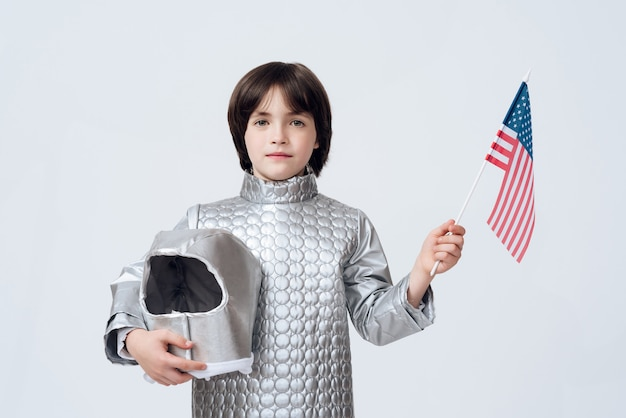 Little boy in cosmonaut costume with usa flag in hand.