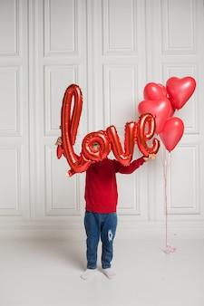어린 소년은 흰색 바탕에 빨간 풍선 사랑으로 자신을 덮었습니다.