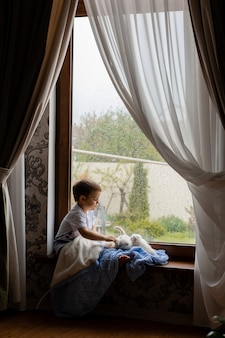 Little boy covered with blue knitted blanket is sitting on the windowsill with white fluffy kittens