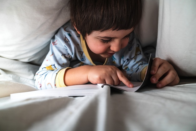 Little boy covered with the sheets of his bed at night with his pajamas on, happily reading a book