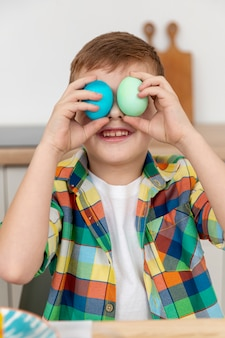 Little boy covering eyes with painted eggs