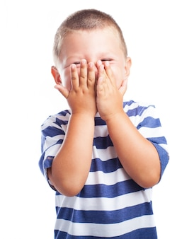 Little boy covering his face with both hands