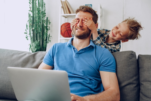 Маленький мальчик закрывает глаза отца руками в гостиной дома