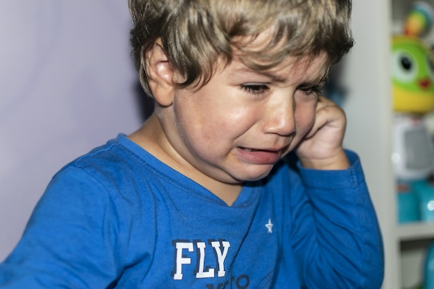 Little boy crying in frustration at not being able to do his homework tdh concentration problems tan...