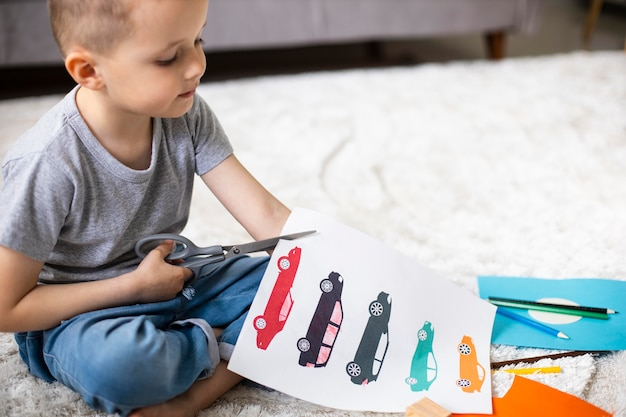 Little boy cutting a paper with car drawings