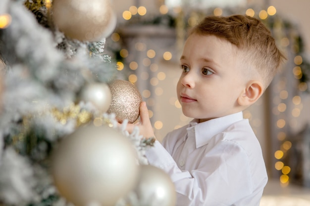Little boy decorates a christmas tree for christmas
