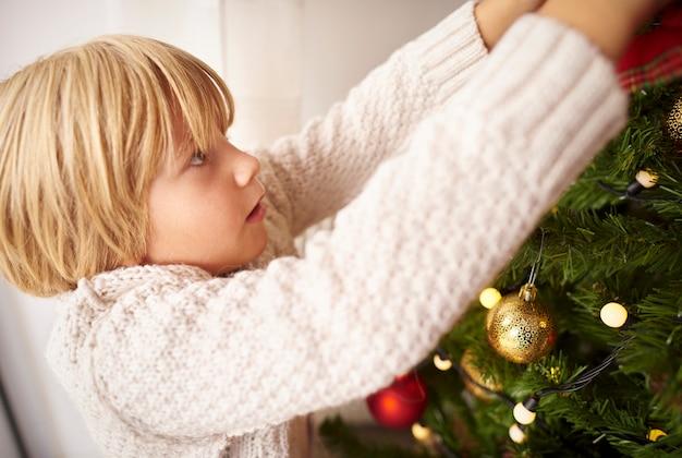 집에서 크리스마스 트리를 장식하는 어린 소년