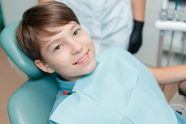 Little boy in dental chair. patient at dentist's office after treatment.