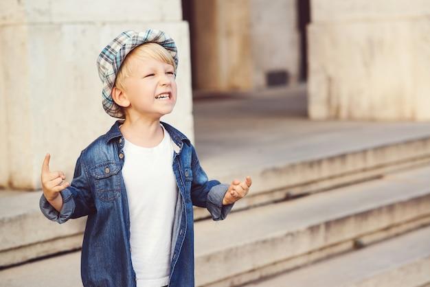 야외에서 헤비메탈 록 사인을 묘사한 어린 소년. 어린 시절 라이프 스타일 개념입니다. 데님 재킷과 모자를 쓴 아이. 도시를 산책하는 세련된 소년