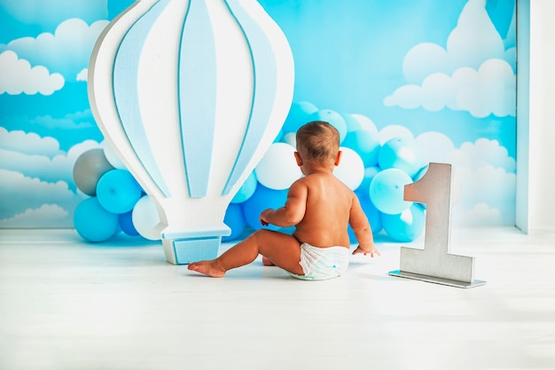 A little boy in diapers sits on the floor next to a large number one and blue balloons