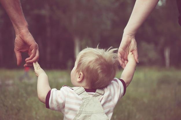 Маленький мальчик делает свои первые шаги с помощью мамы и папы в летнем парке