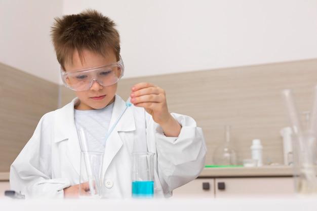 Маленький мальчик делает эксперимент в школе