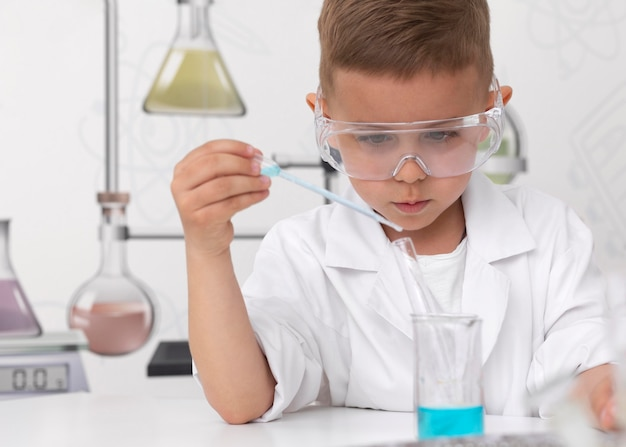 Little boy doing an experiment at school Premium Photo
