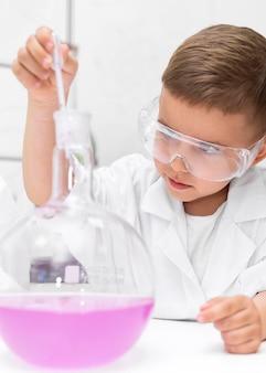 Little boy doing an experiment at school