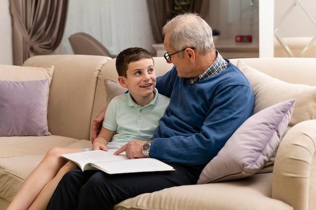 집에서 그의 할아버지와 함께 숙제를 하 고 어린 소년