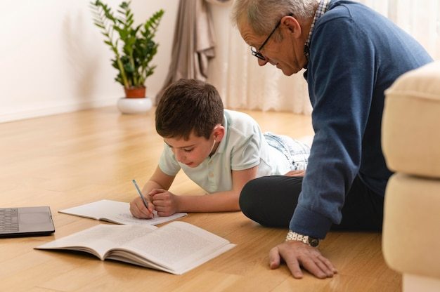 Little boy doing homework with his grandfather at home