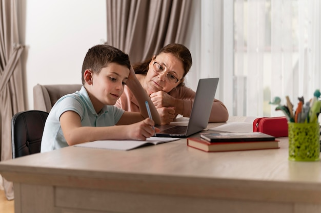 Little boy doing homework with his grandmother on laptop