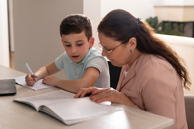 Little boy doing homework with his grandmother