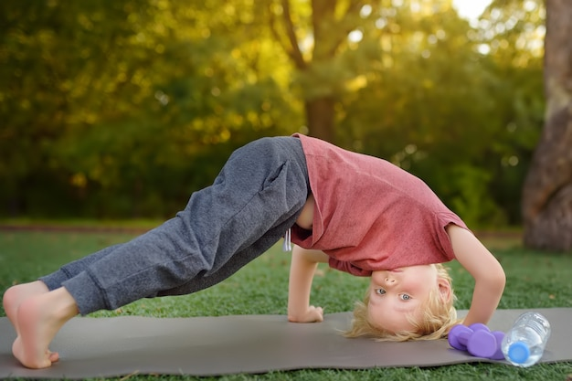 Little boy doing stretch during workout outdoors