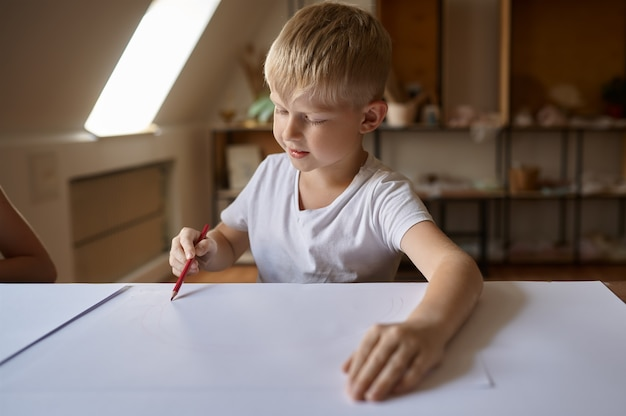 Маленький мальчик рисунок за столом, ребенок в мастерской. урок в художественной школе. молодой художник, приятное хобби, счастливое детство. творческое развитие