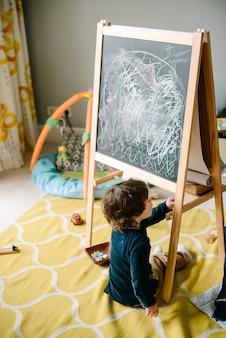 床に座って黒板にチョークを描く少年