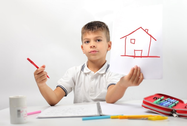 Little boy drawing a house