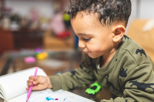 Little boy drawing on a notebook