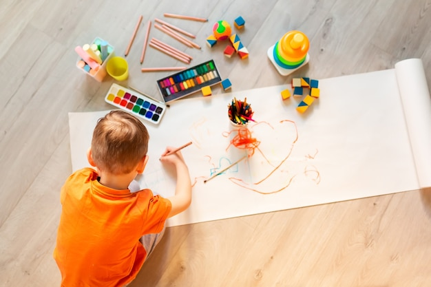 Little boy drawing a picture on the floor in his room, top view. children's art and creativeness concept