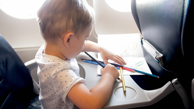 Little boy drawing picture on table in airplane.