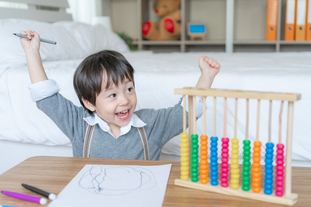 Little boy drawing in white paper with enjoying Free Photo