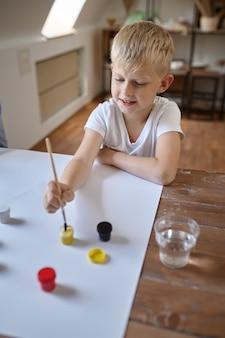 Маленький мальчик рисунок гуашью за столом, ребенок в мастерской. урок в художественной школе. молодой художник, приятное хобби, счастливое детство