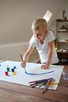 Маленький мальчик рисует гуашью на лице
