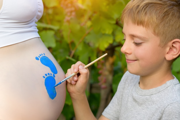 Little boy draws with a brush on the belly of his pregnant mom babyã¢â€â™s footprint. pregnant concept. close-up