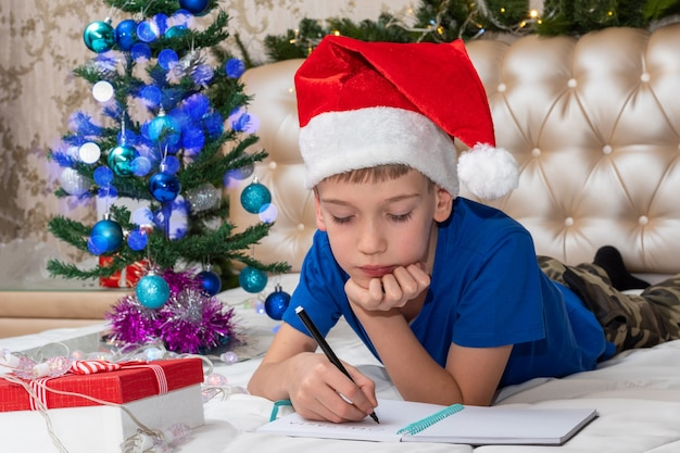 A little boy dreams of gifts and writing a letter to santa at home, multi-colored bokeh, a red gift box