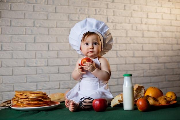 台所で料理人に扮した少年。リンゴを食べるエプロンに身を包んだハンサムな子供