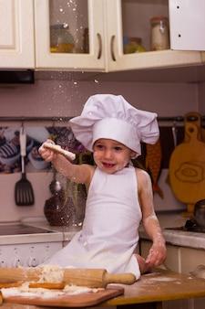 料理人に扮した少年が小麦粉生地をこねる