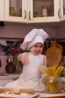 料理人に扮した男の子が台所のテーブルに座って、ふわふわと遊ぶ