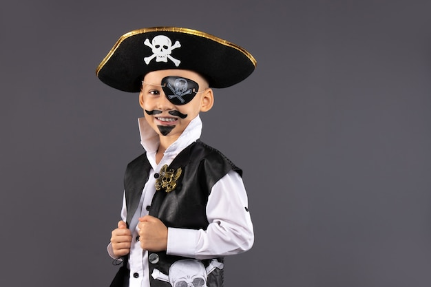 Little boy dressed as a pirate with makeup on his face is having fun at a halloween party. .