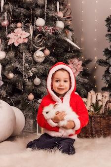 산타클로스 옷을 입은 어린 소년이 크리스마스 트리 근처에서 토끼를 손에 들고 있다